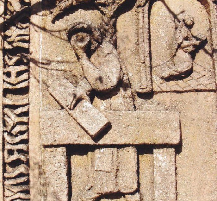 1 van de keramische tegels die ingemetseld zijn in de muur om de begraafplaats heen.